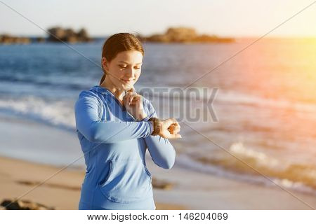 Runner woman with heart rate monitor running on beach
