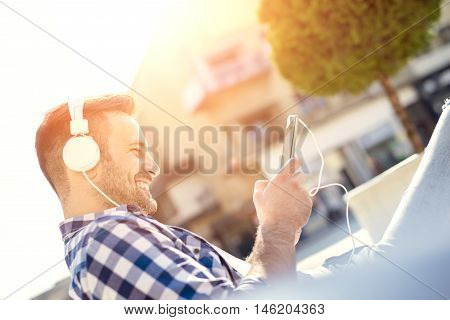 Close up of a young man sitting outdoors listening to music.He is enjoying the music.