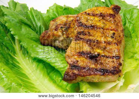 pork chops grilled golden brown on romaine lettuce leaves