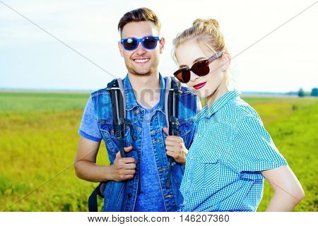 Hitchhiking couple. Happy young people standing on a highway.