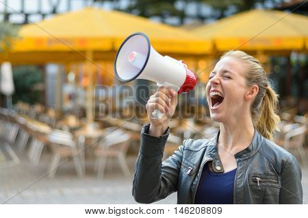 Young woman yelling into a megaphone or bullhorn as she stands outside airing her grievances while participating in a protest