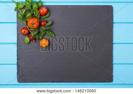 Fresh tomatoes and basil on a black slate. . Space for text.
