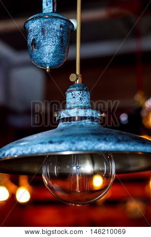 Old grunge blue lamp with wide lampshade and round glass bulb
