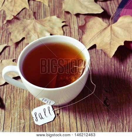 closeup of a white ceramic cup with a bag of tea or herbal tea being soaked in hot water, with the word fall written in its label, on a rustic wooden table with some dried leaves