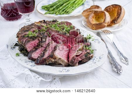 Sliced Porterhouse Steak with Yorkshires and Green Asparagus on Plate