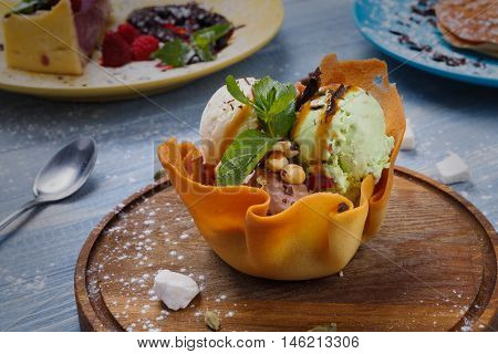Restaurant refreshing dessert. Ice cream served in waffle bowl. Three colored ice-cream scoops with mint, peanuts and chocolate sauce on wooden desk.