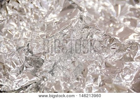 Silver foil background with shiny crumpled surface texture background