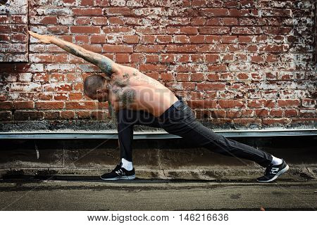 Experienced yoga man doing various yoga poses outdoor by the brick wall. Yoga concept.