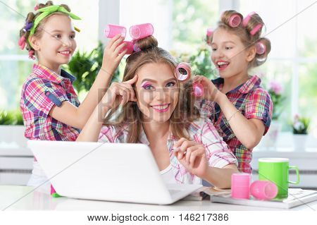 Cute  tweenie girls and mother  in hair curlers  with laptop at home