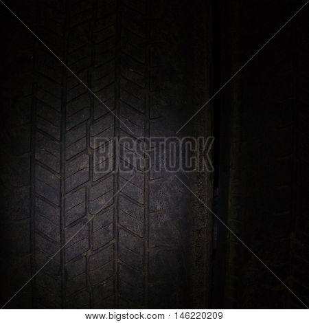 Car tires in a row on a shelf tire. Close-up in dark.