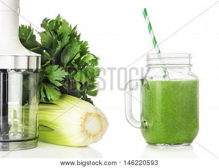 Blender stems and leaves of celery and green smoothies in jar isolated on white background healthy eating concept