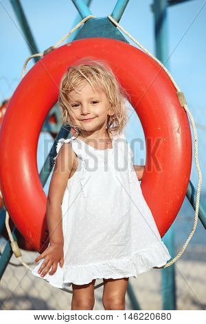 Little girl in white dress smiling and holding a red life buoy on the beach