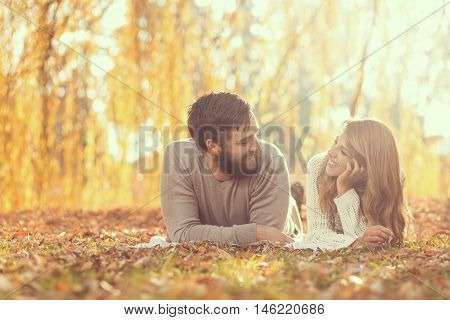 Couple in love lying on fallen autumn leaves under a tree in a park enjoying a wonderful autumn day in nature. Focus on a man