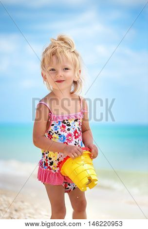 Little caucasian white girl two years old in a bright swimsuit at the beach near the sea playing with a bucket