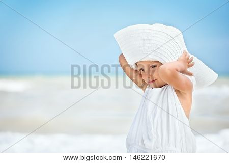 Little caucasian white pensive girl two years old in a white mothers dress and hat looking away at the beach near the sea close up