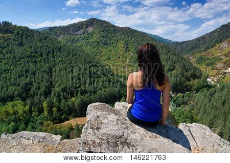 A girl is sitting on the edge of a cliff and looking at a mountain