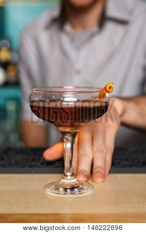 Unrecognizable barman offers alcohol cocktail in night club. Professional male bartender at work in bar made a drink for party. Focused on glass