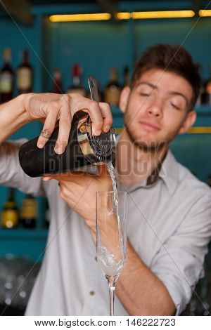 Young handsome barman in bar interior pouring alcohol cocktail drink into glass. Professional bartender at work in night club. Service industry occupation. Vertical image