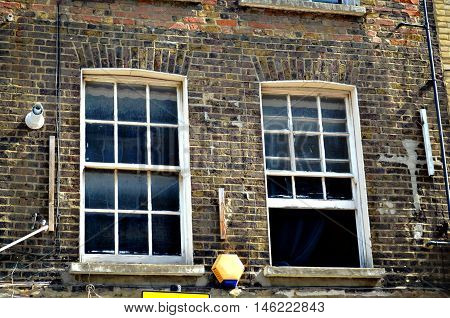 two typical British windows in a brick wall opened and closed Uk London