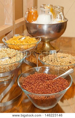 Buffet variety of cereals for breakfast-cereals in glass bowls, milk and juice in glass pitchers, vertical