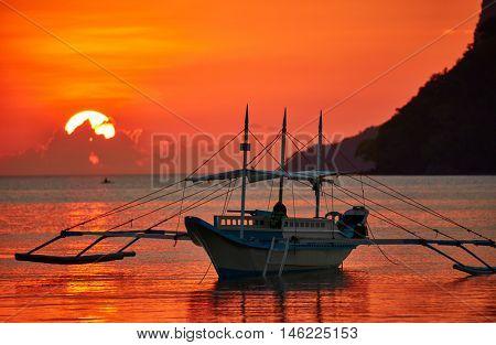 Traditional filippino boat at El Nido bay in sunset lights. Palawan island, Philippines