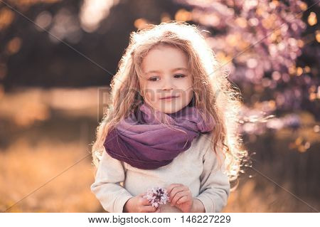 Cute baby girl 3-4 year old holding flower wearing stylish clothes outdoors.
