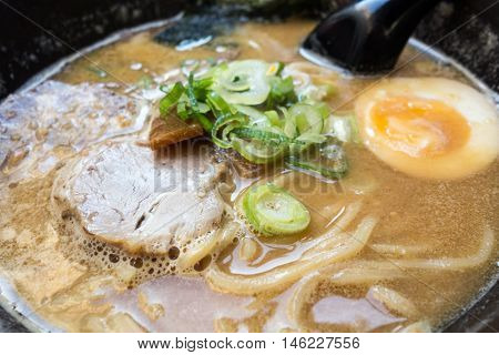 Tasty Japanese ramen soup bowl with pork, egg, and vegetables