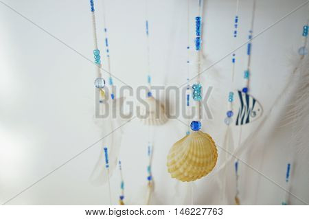 photo of a handmade white and blue pendants with feathers, beads, wooden fish and seashells, on a white background