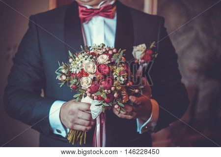 Concept image - groom waiting for bride with a bouquet