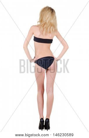 Beautiful young woman in bathing suit looking at wall. Rear view.