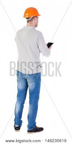 young engineer in a protective helmet with tablet computer in the hands of. Rear view people collection.  backside view of person.  Isolated over white background. Engineer verifies the work done with