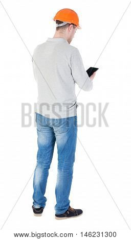 young engineer in a protective helmet with tablet computer in the hands of. Rear view people collection.  backside view of person.  Isolated over white background. engineer is reporting in the tablet