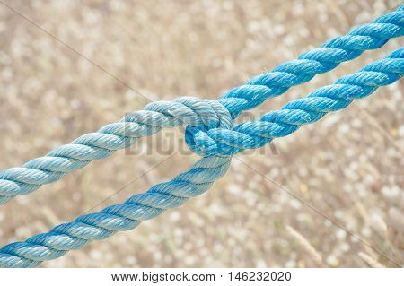 Two blue nylon ropes and straps used interlaced