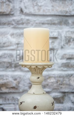 Vintage candlestick with stone wall background in HDR.