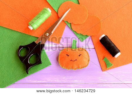 Halloween mini pumpkin ornament. Orange felt pumpkin, scissors, flat pieces of felt, green and black thread, needle on wood background. Halloween sewing crafts. Idea for kids. Top view