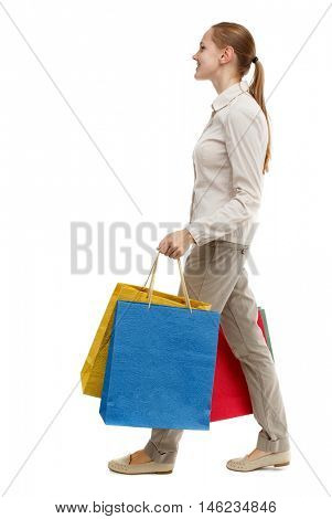 side view of going woman with shopping bags . Rear view people collection. Isolated over white background. Skinny girl in white jeans walks past with purchases.