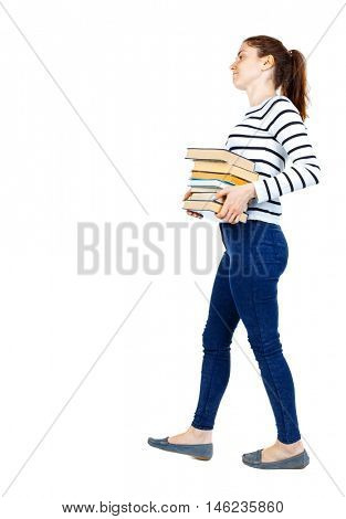 Girl comes with stack of books. side view. Rear view people collection. Girl in a striped sweater goes to the side while holding heavy books.