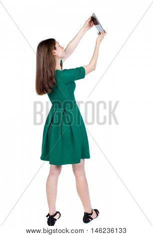 back view of standing young beautiful woman using a mobile phone. girl watching. backside view of person. slender brunette in a green short dress takes on something at the top of the plate.