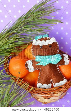 Felt gingerbread man. Handmade felt Christmas gingerbread man on the basket with mandarin nearby pines