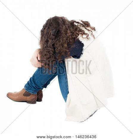 back view curly girl sitting and crying. girl relaxes. Rear view people collection. backside view of person. Isolated over white background.  A girl in a white tank top sitting on the floor with his