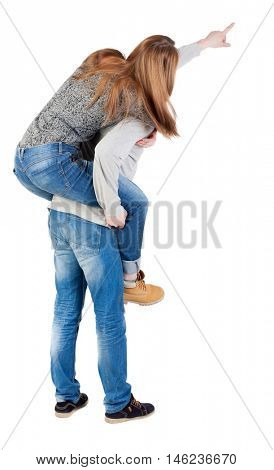 young couple pointing at wal Back view  (woman and man). Rear view people collection.  backside view of person.  Isolated over white background. The girl is sitting on the back of his hand and points