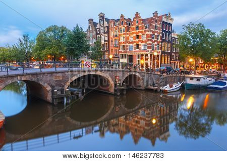 Amsterdam canal, bridge and typical houses, boats and bicycles during morning twilight blue hour, Holland, Netherlands.