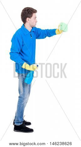 side view of a cleaner man in gloves with sponge and detergent. girl watching. Curly boy in the blue jacket cleans.
