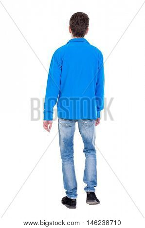 Back view of going handsome man. walking young guy . Curly boy in a warm blue sweater goes out of frame.