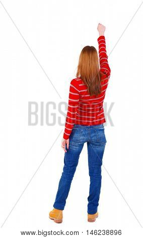 Back view of woman. Raised his fist up in victory sign. Raised his fist up in victory sign. blonde in a red striped sweater standing with a raised hand.