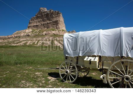 A covered wagon sits by Scotts Bluff National Monument depicting how settlers passed through the area on their migration west on the Oregon Trail in Nebraska.