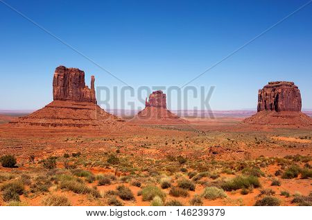 Three sandstone buttes in Monument Valley Utah is part of the Navajo Tribal Park Reservation and is frequently used as a movie location in western desert scenes.