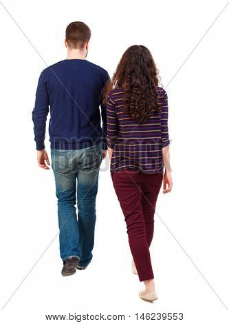Back view going couple. walking friendly girl and guy holding hands. Swarthy girl and the bearded man into the distance.