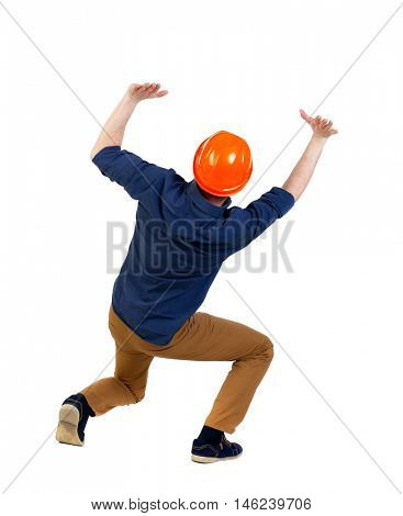 back view business man protective construction helmet protects hands from what is falling from above. Isolated over white background. a man wearing a helmet holds a heaviness above your head.