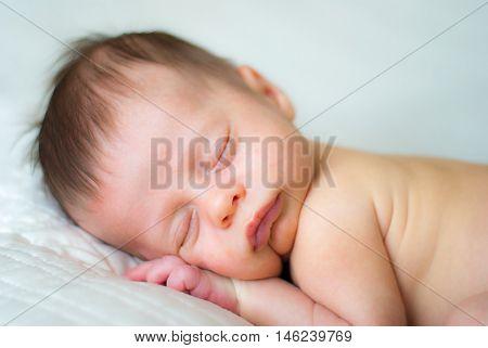 Newborn Baby Boy Sleeping on White Blanket